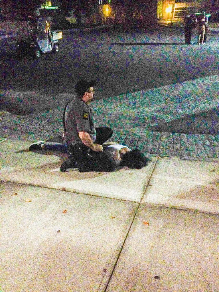 A Public Safety Officer subdues one of the three girls involved in a fight outside of the Homecoming Dance