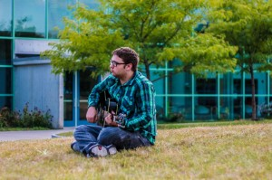 Michael Sweeney strums along in front of Guenther Hall.