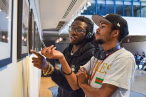 Students ponder the 'Life Behind the Scenes' exhibit located in the Dwight Marvin Library Atrium.